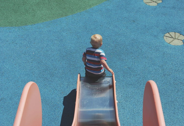 Rear view of boy playing on slide at playground