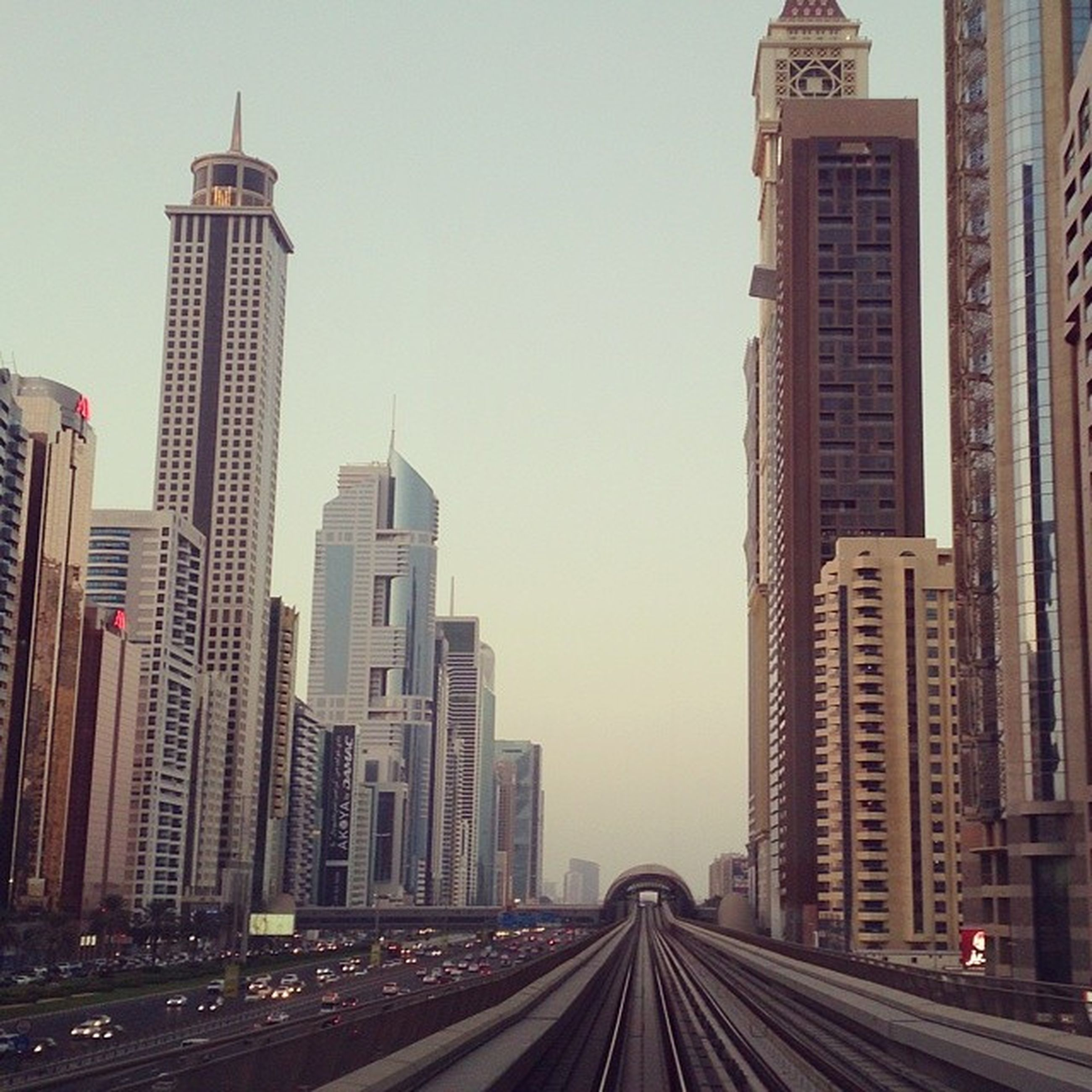 building exterior, architecture, built structure, city, the way forward, skyscraper, transportation, tall - high, tower, diminishing perspective, road, modern, office building, street, cityscape, vanishing point, clear sky, sky, city life, car