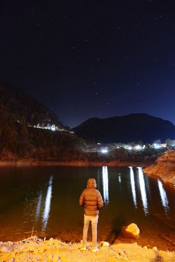Rear view of man standing by lake against sky at night