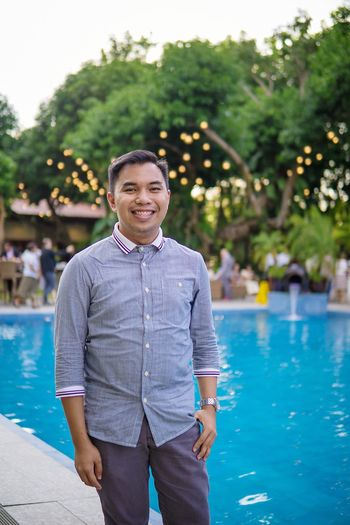 Portrait of young man standing by swimming pool