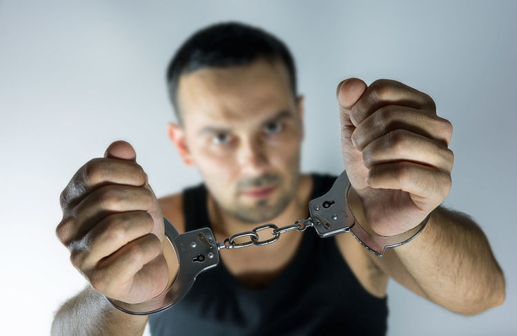 Adult man with handcuffs Adult Arrested Handcuffs  Man Male Young Prison Jail Crime Thief OutLaw Arrest With Handcuffs Burglar Illegal Activity Punishment Sentence Man Arrested People Looking At Camera Young Adult One Man Only Fist Handcuffed Justice