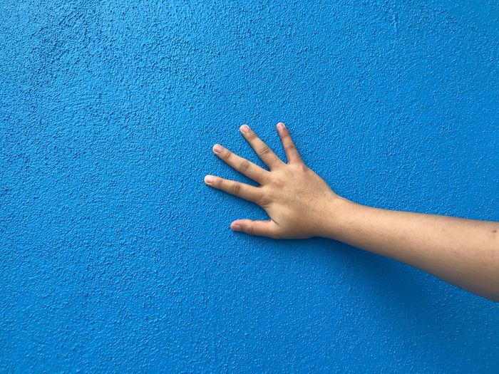 Cropped hand touching blue wall