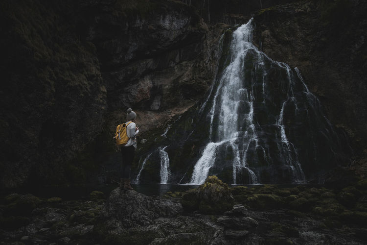 Woman on rock looking at waterfall
