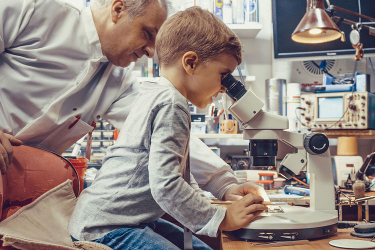 Science teacher and small boy analyzing circuit board under a microscope in it laboratory.