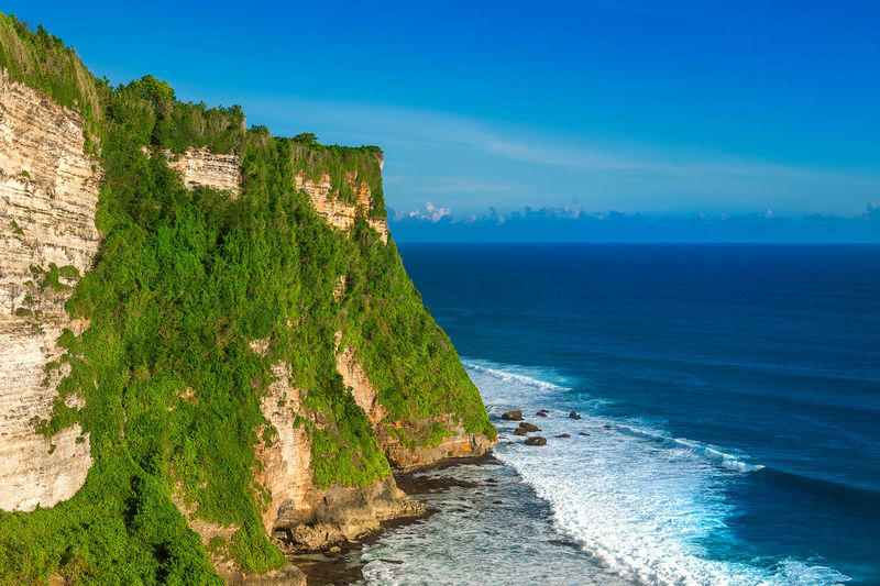 Scenic view of cliff by sea against sky at uluwatu