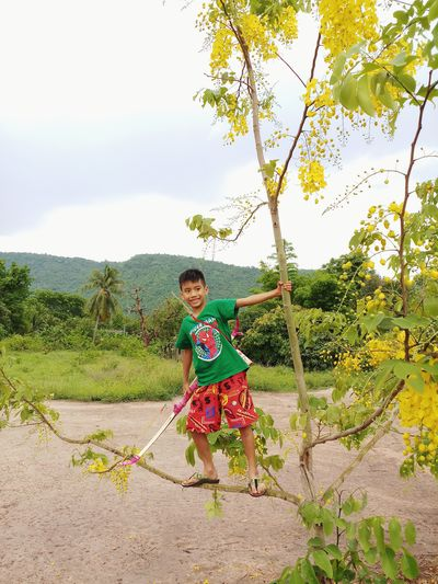 Smiling Boy Standing By Tree Against Sky