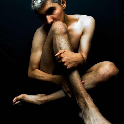 Full length of shirtless man sitting against black background