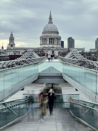 People walking in modern building over bridge against sky in city