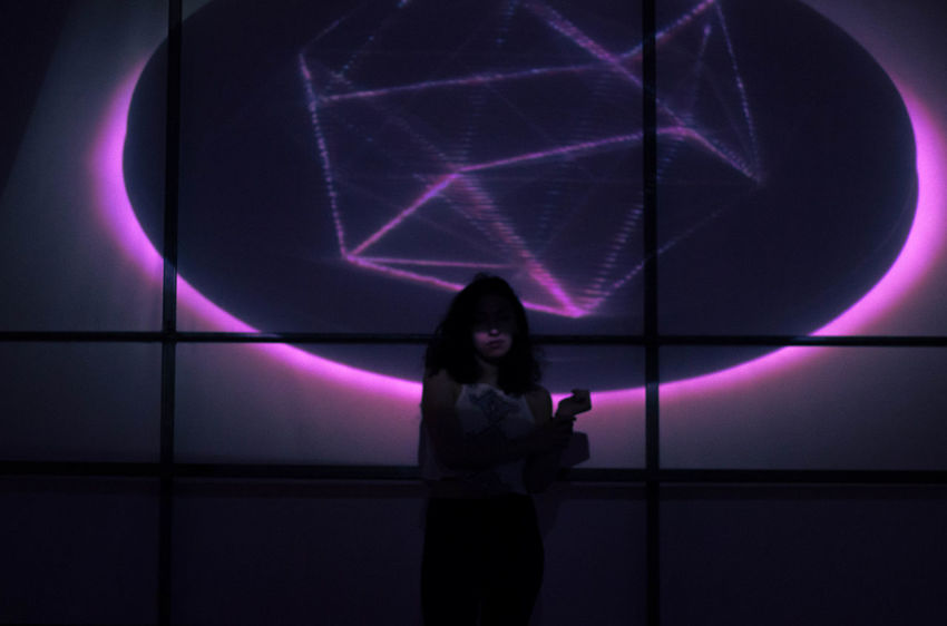 Arts Culture And Entertainment Child Childhood Dark Emotion Enjoyment Females Glowing Illuminated Indoors  Laser Light Night Nightlife Offspring One Person Projection Purple Real People Silhouette Sitting Standing Women