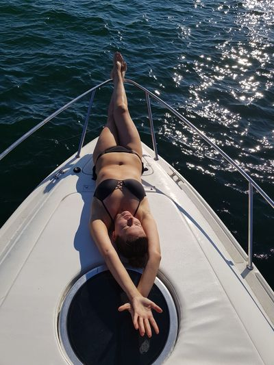 Woman lying on boat in sea