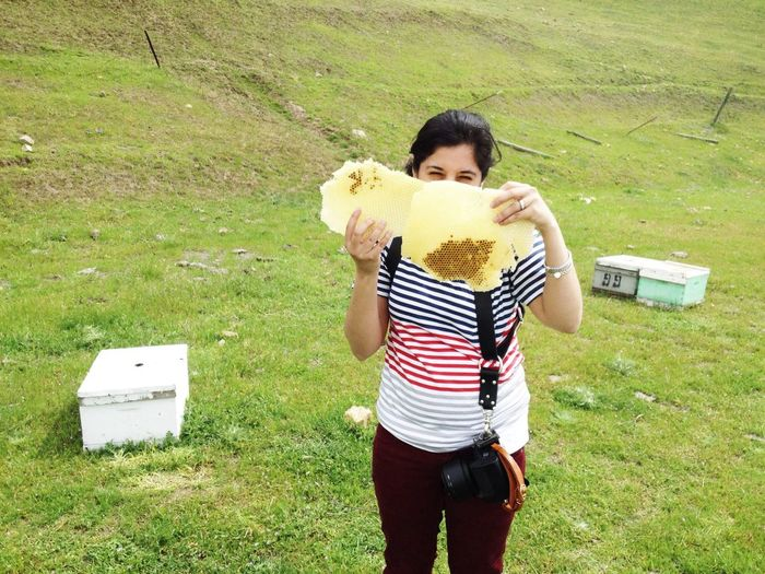 Portrait of a young woman holding hive on grassland
