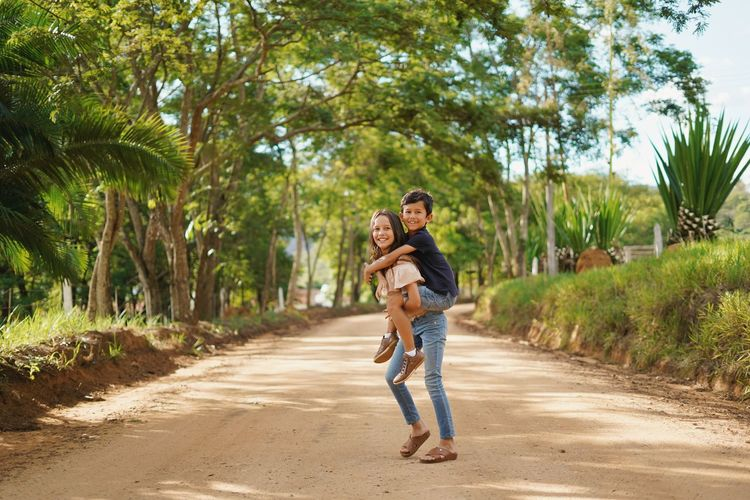 Full length portrait of smiling sister carrying brother on back on road