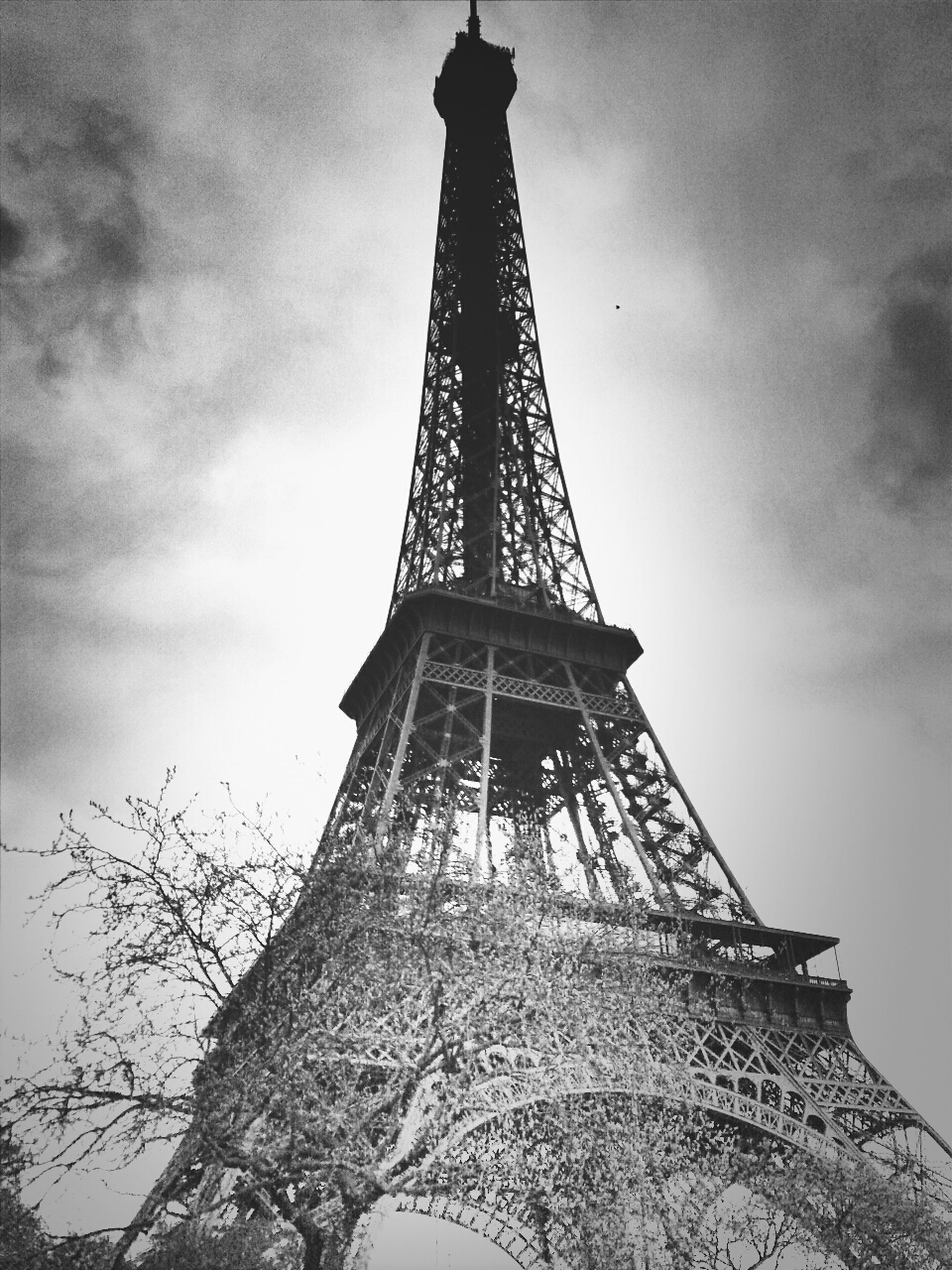 low angle view, eiffel tower, sky, tower, tall - high, built structure, architecture, metal, cloud - sky, culture, international landmark, famous place, metallic, travel destinations, tall, capital cities, cloudy, tourism, history, travel
