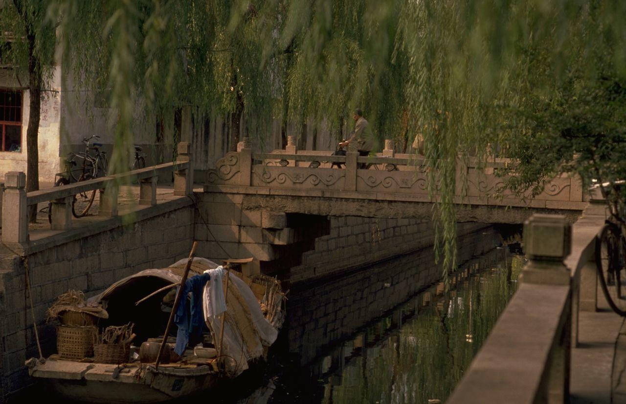Boat In Canal Against Footbridge