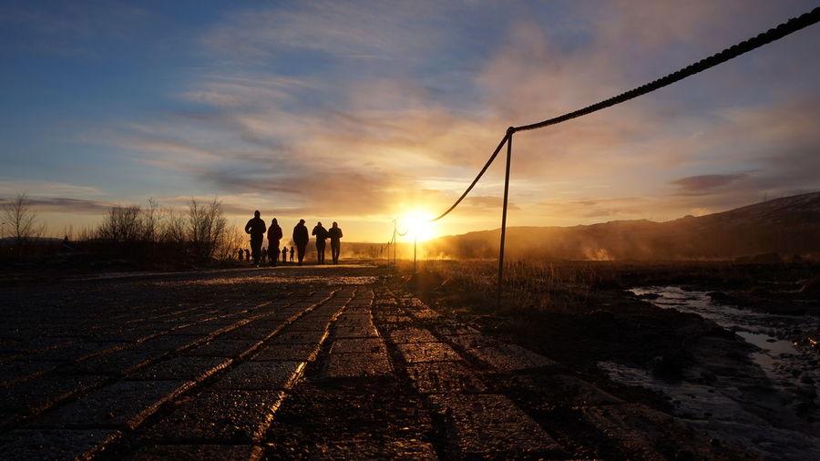 Men on road against sky during sunset