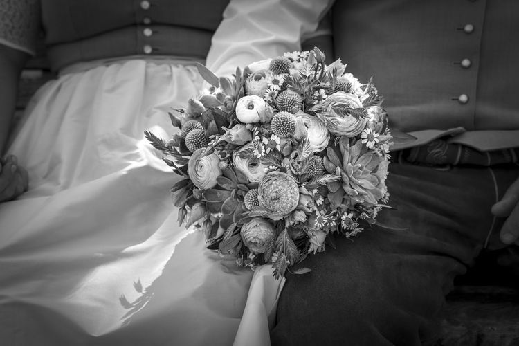 Close-up of woman holding bouquet against white wall