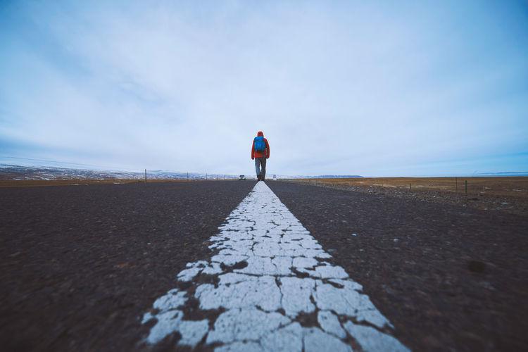 Rear view of man walking on road against sky