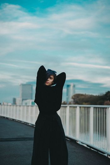 Portrait of woman standing by railing against sky