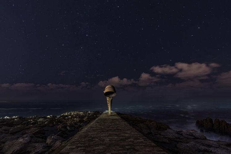 Seaside sculpture against sky at night