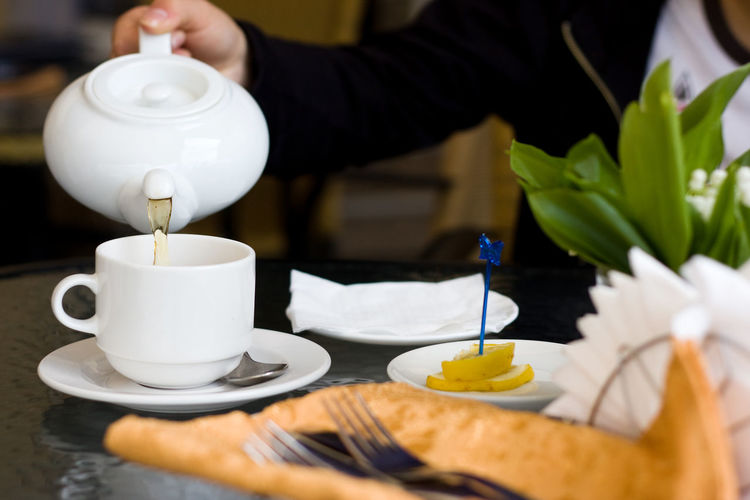 White cup and teapot with green tea in cafe Adult Adults Only Afternoon Tea Cafe Close-up Cups Day Dining Table Drink Eating Flowers Food Food And Drink Green Tea Human Body Part Human Hand Indoors  Lemon Lunch People Table Tea - Hot Drink Teapot