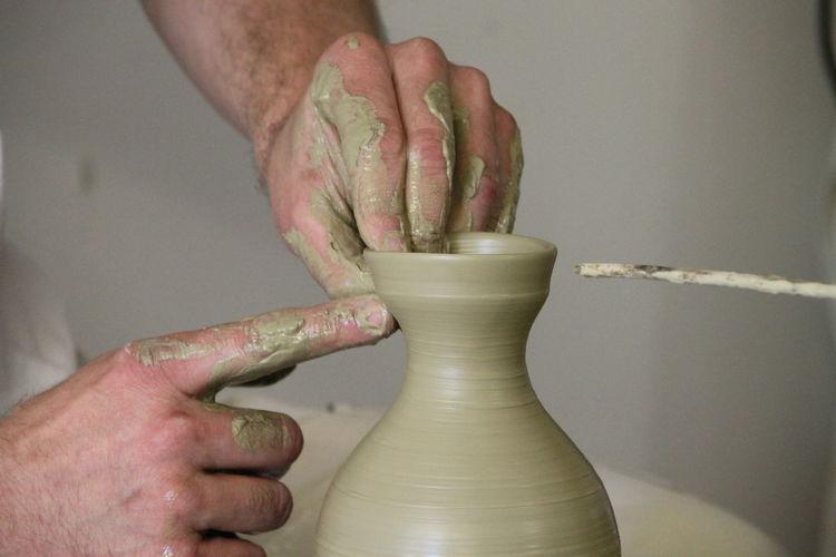Cropped Hands Of Potter Making Pot In Workshop