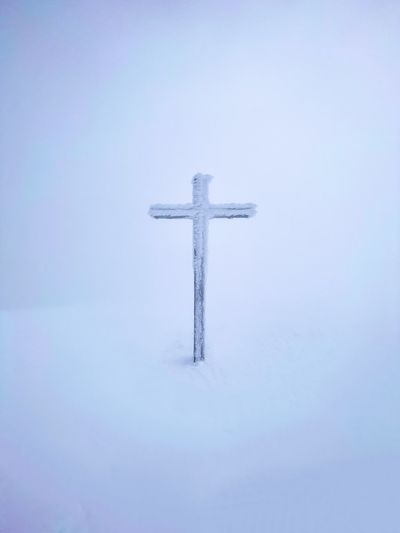 Cross on snow covered field against sky