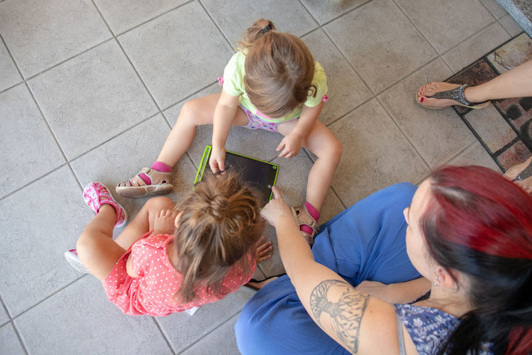 High angle view of women sitting on tiled floor