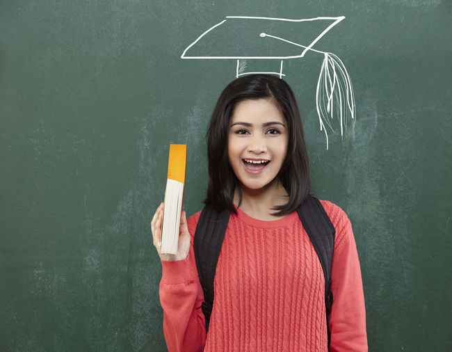 student with text book stand in front of blackboard Adult Blackboard  Casual Clothing Chalk Drawing Cheerful Classroom Day Drawing Education Front View Green Color Happiness Indoors  Learning Looking At Camera Mortar Board One Person People Portrait Smiling Standing Student University Student Young Adult
