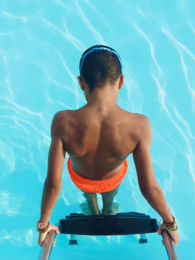 High angle view of shirtless boy standing on ladder in swimming pool
