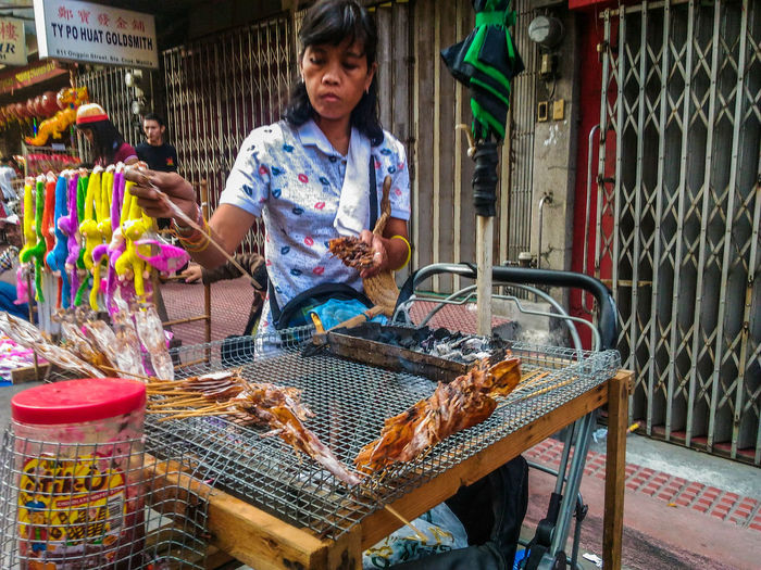 Female vendor with dried calamari for sale at footpath