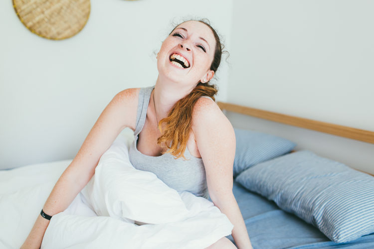 Mid adult woman laughing while sitting on bed at home