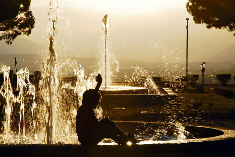 Silhouette woman sitting on fountain