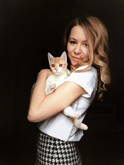 Portrait of woman with cat against black background