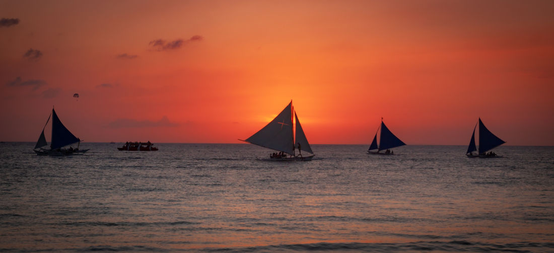 Sailboats sailing in sea against orange sky
