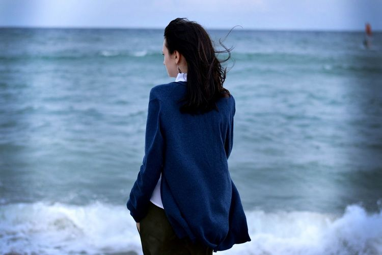 Rear view of woman standing against sea