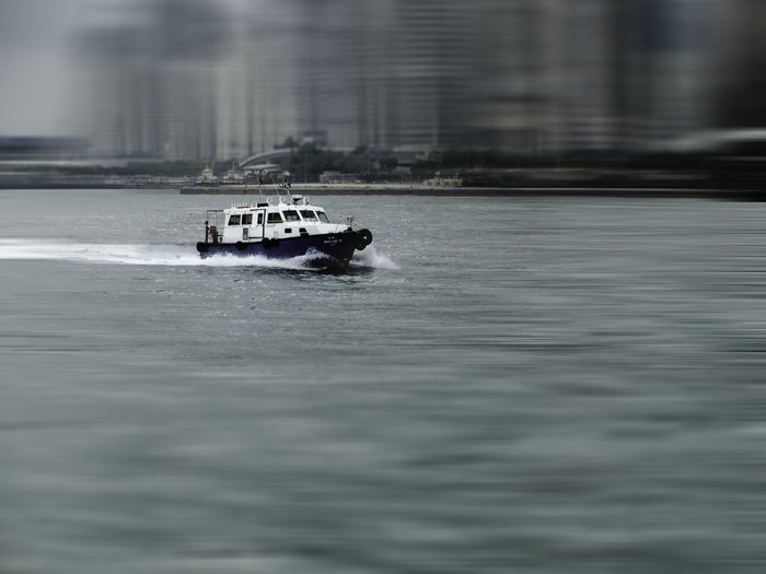 Boat in river against blurred buildings