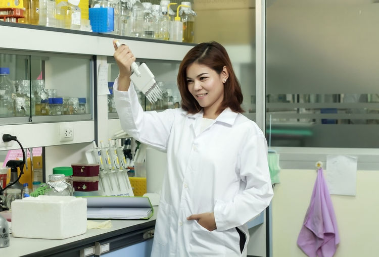 Smiling Scientist Performing Experiment At Laboratory
