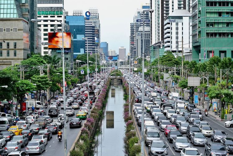 Traffic Jam Architecture Building Building Exterior Built Structure Car City City Life City Street Cityscape Day High Angle View Incidental People Land Vehicle Mode Of Transportation Modern Motor Vehicle Office Building Exterior Outdoors Road Skyscraper Street Traffic Transportation Tree