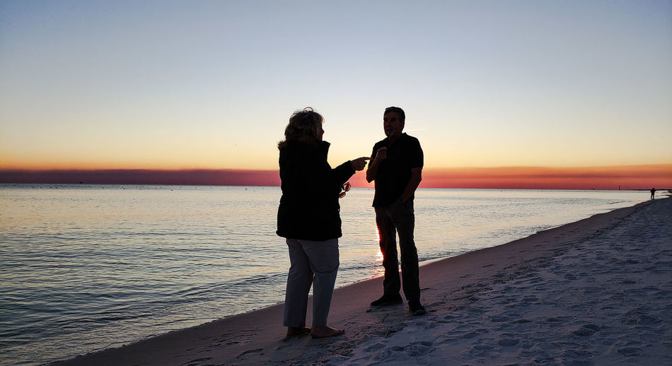Silhouette friends talking while standing on beach against clear sky during sunset