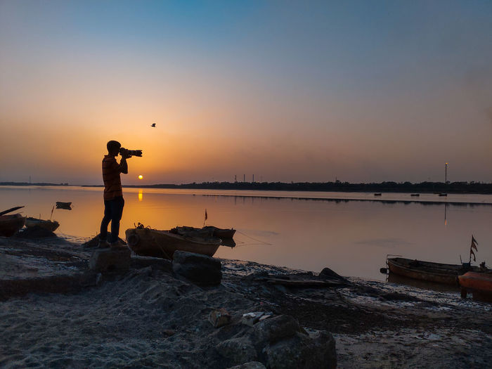Man photographing on rock at beach against sky during sunset