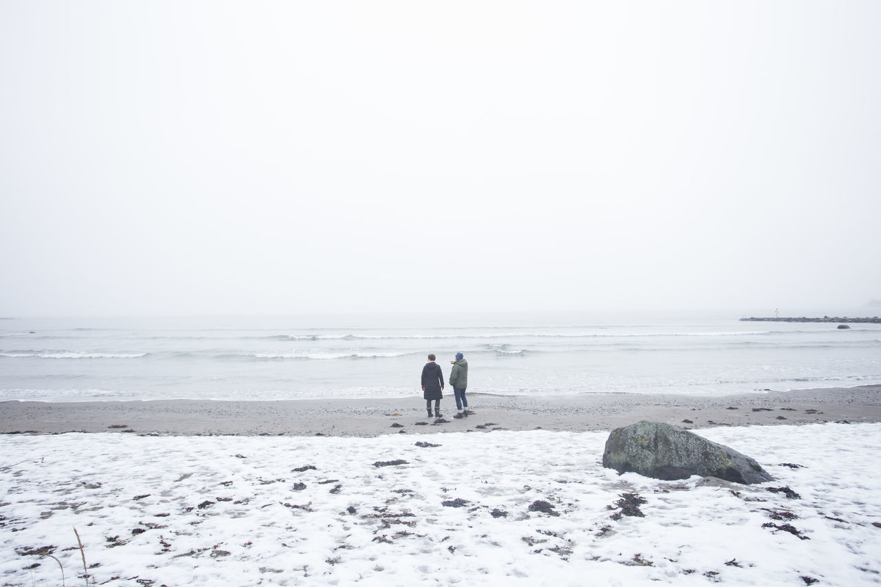 REAR VIEW OF TWO PEOPLE WALKING ON BEACH