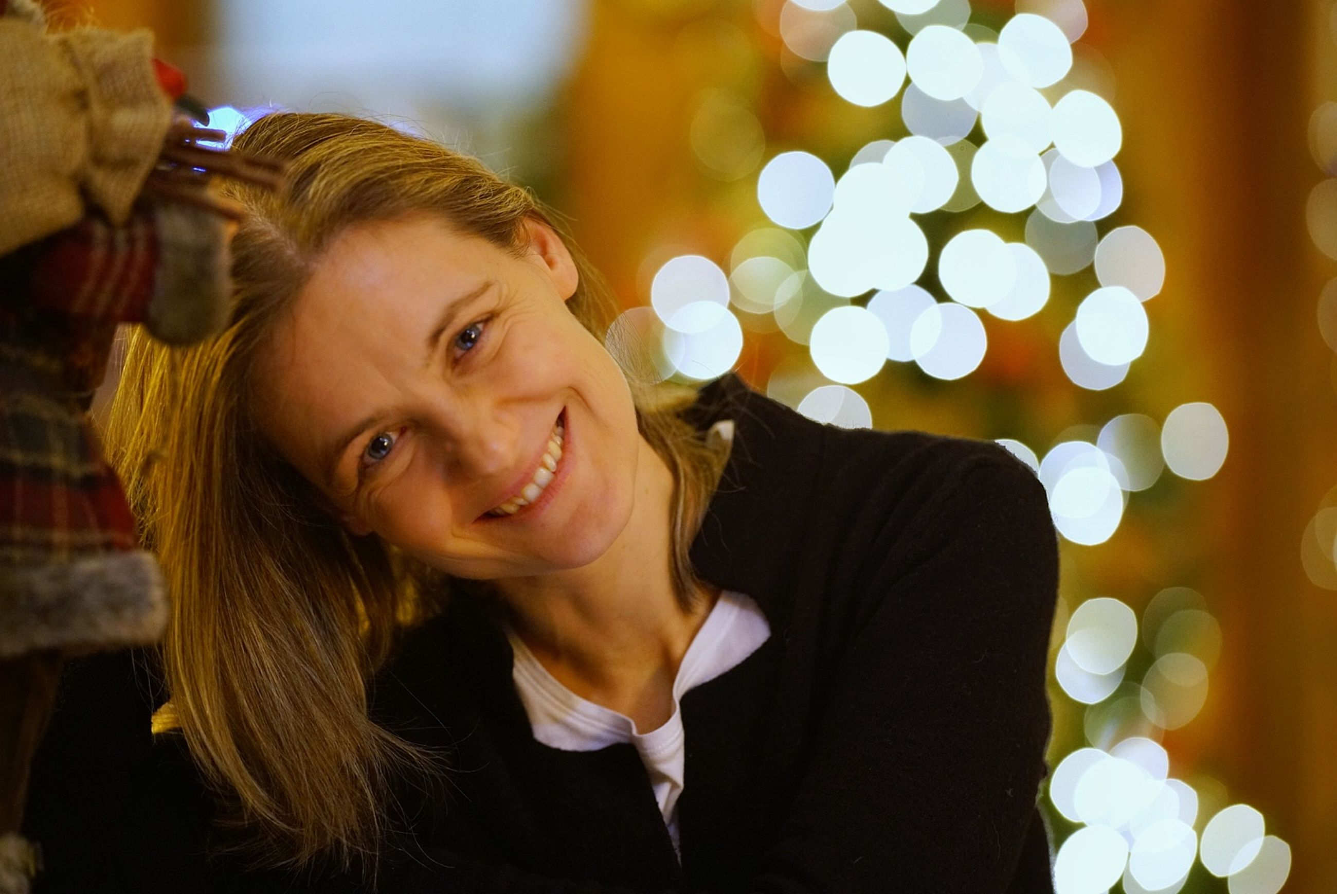 smiling, portrait, happiness, emotion, one person, christmas, women, headshot, young women, young adult, illuminated, focus on foreground, hair, lifestyles, real people, beauty, looking at camera, christmas tree, celebration, beautiful woman, hairstyle