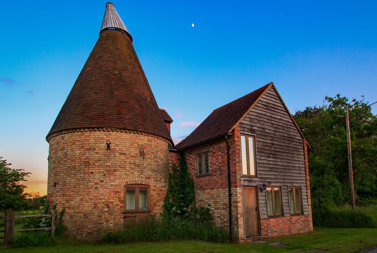 Oast House,Garden of England, Kent, England. Plant Nature No People Built Structure Architecture Building Exterior Outdoors Building Hops Beer Brewing Travel Destinations Tourism Caravan Rural Scene Countryside EyeEm Gallery Vivid International Getty Images Architecture Iconic Buildings Sky History Day The Past Old Blue Tree Clear Sky Grass Place Of Worship Land