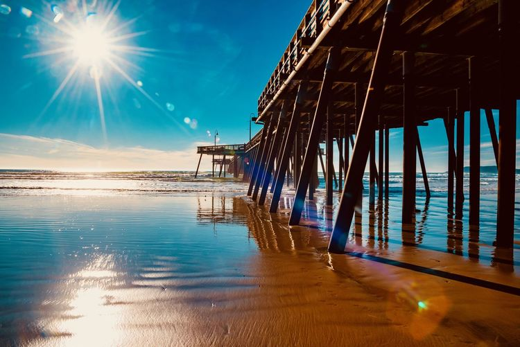 Water Sky Architecture Built Structure Sea Nature Sunlight Reflection No People Pier Lens Flare Beauty In Nature Tranquility Scenics - Nature Sun Beach Tranquil Scene Sunbeam Outdoors Bright