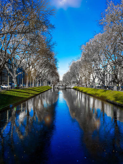 Canal amidst trees against clear blue sky