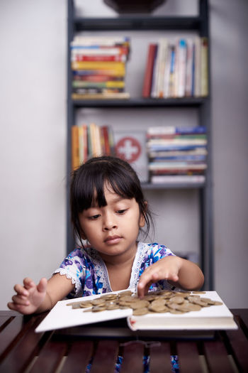 Girl looking away while book on table
