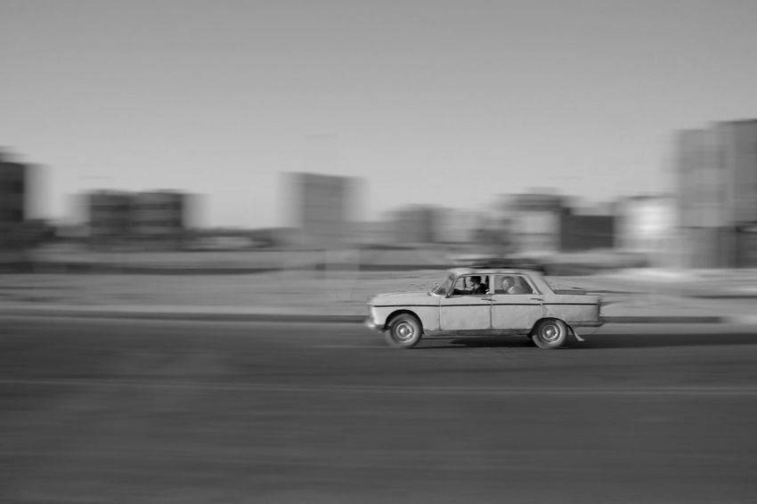 Architecture Blurred Motion Building Exterior Built Structure Car City Copy Space Day Land Vehicle Mode Of Transportation Motion Motor Vehicle No People on the move Peugeot Peugeot 404 Road Selective Focus Sky Speed Street Transportation