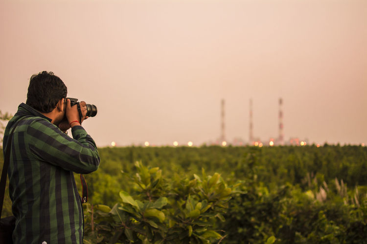 Man photographing through camera while standing on field during sunset