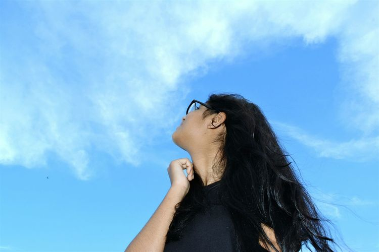 Low angle view of teenage girl against blue sky