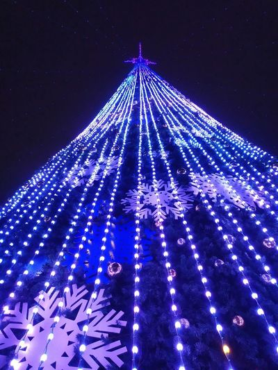 Low angle view of illuminated christmas lights against blue sky at night
